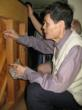 Master Huang , luthier from China, applying his formula to a piano