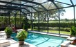 A screen pool enclosure from Venetian Builders, Inc., Miami. Heavier-gauge framing looks elegant look but adds strength.