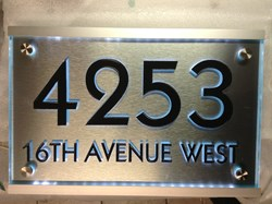 Plasma cut custom stainless steel sign with glass casing and LED lit