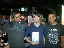 """RJ Mitte (star of the hit television series """"Breaking Bad"""") poses with Black Streak Entertainment's original graphic novel, """"Fiji Random"""" along with Terry and Justin Raimey"""