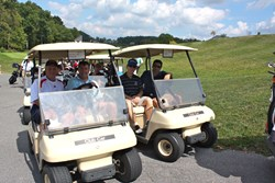 golfers in golf carts prepare to begin the golf tournament to benefit the Make-A-Wish Foundation