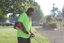 A young man landscaping as part of Auberle's job training program.