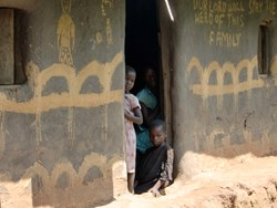 Children watch as their father is tended to by a palliative care worker in a remote Ugandan village.