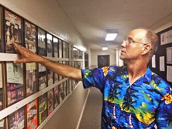 Don Hooper points to past playbills in the Marjorie Lyons Playhouse