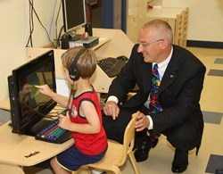 Four-year-old Colton Liberto shows Standard Process President Charles C. DuBois how to work on an interactive computer in his classroom.