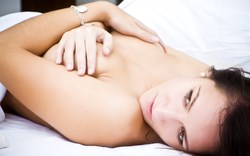 Beautiful caucasian woman lying down and holding naked breasts