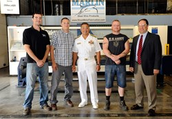 "U.S. Navy Rear Admiral Anatolio B. ""A.B."" Cruz III poses with Marlin Steel employees and military veterans Josh Wallace, Eric Courtright and Bill Ison along with Marlin Steel President Drew Greenblatt in front of the company's sheet-metal laser."