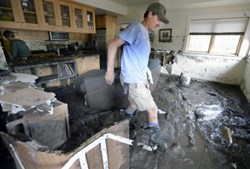 Man inspects a mud-filled basement after Colorado flooding