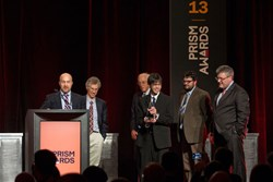 TeraDiode CEO Parviz Tayebati and VP Sales/Marketing Jay Liebowitz (at podium) accept their Prism Award from Jenoptik CEO, Photonics21 President and German Gov't Commissioner Michael Mertin, at right.