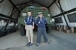 """Two cub scouts stand in front of the RRPD """"Bear,"""" our SWAT vehicle."""