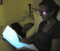 Lady reading in bed wearing new LED Glasses