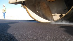 Fine-graded asphalt being compacted by a roller.
