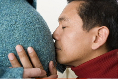 Father kissing pregnant mothers belly.
