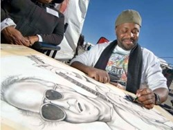 An artist draws at the Festival of the Arts.
