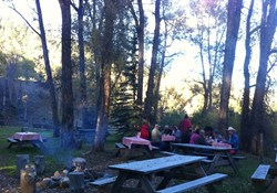 Saturday night steak dinner by the river with guests at Rainbow Trout Ranch.