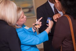 Marci McCarthy showing the app to an executive attendee at an event.