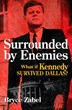 """Surrounded by Enemies: What if Kennedy Survived Dallas?"" by Bryce Zabel. The alternate-history novel is available as a trade paperback, eBook and audiobook."