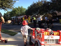 Boy next to toy fire truck watches as professional firefighters clean up after successfully putting out a house fire.