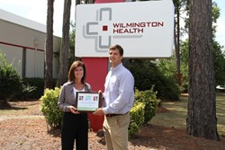 Jennifer Byrne presents Dr. Kevin Cannon with a plaque commemorating the partnership