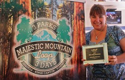Rhonda Salisbury with the Yosemite Sierra Visitors Bureau shows the Best Idea Award from the Western Associatio of Convention and Visitors Bureau's alongside a display screen for the Majestic Mountain Loop, the idea that won the distinction.
