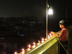 Lighting Diwali candles on a rooftop in Varanasi