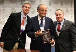 Professor Arne Ljungqvist receiving a plaque from Dr. Steven Ungerleider and David Ulich.