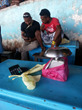 Judah Suimae interviews a reef fish vendor at the Honiara Central Market using the Hapi Fis mobile app, powered by Point 97.