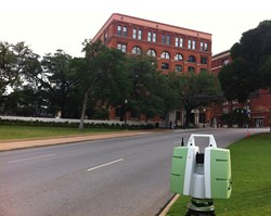 The Leica ScanStation in Dealey Plaza, the location of President John F. Kennedy's assassination. The sixth floor corner window of the Texas School Book Depository (now a museum) is visible just above the tree line.
