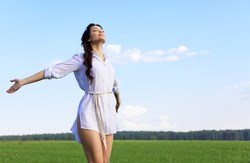 Woman standing in a field with her arms outstretched