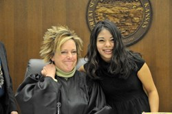 Johnson County, Kansas judge Kathleen Sloan smiles with a child who has just been adopted with the support of KVC Health Systems.