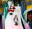 Santa slides down the Yule Slide with a little princess