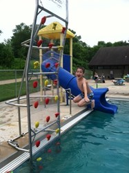 Camper makes a Kersplash at the Pool Climbing Wall at Camp Butwin