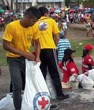Scientology Volunteer Ministers in their bright yellow shirts, delivering  food to those in need in Tacloban in the Philippines