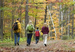 family on hiking trail facing away