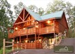 large log cabin with lights on at sunset
