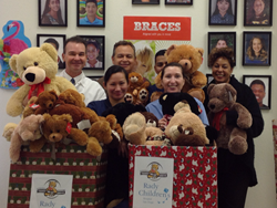 SmileCare orthodontist Dr. Geoffrey Kopecky (back row, left) and team members from 8 offices donated teddy bears to benefit Rady Children's Hospital.