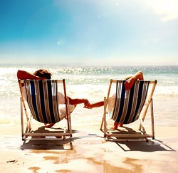 couple holding hands on beach in chairs