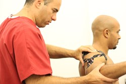 dr shoshany using rocktape to help assist the shoulder joint