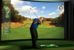 Golfer takes a swing on golf simulator while dining.