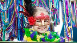 A photo of a kid in a Mardi Gras mask