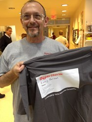 "35-year Hypertherm Associate Larry Benson shows off his new t-shirt with a business card that proudly proclaims his new job title: ""owner."""