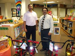 Two men standing near bicycles in school library