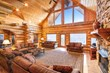 log cabin living room with furniture and large windows