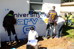 Students and instructors from UACDC's Prodigy cultural arts program paint the mural on the Harvest Hope Center.