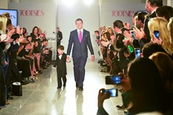 Johnny Manziel walking hand in hand with 6-year-old cancer survivor Charlie Dina at Tootsies Love's in Fashion.