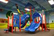 Slides, climbers, interactive panels and under-deck seating make this a fun spot for children to gather and play indoors!