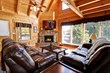 living room of log cabin overlooking mountains and forest