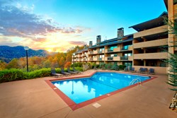 condo building with swimming pool and sunshine in the smokies