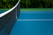 Two lit tennis courts on property.