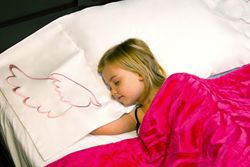 A little girl sleeps comfortably using PilloWings 3-in-1 Pillowcase, Pillow Sham, and Part Bed Sheet